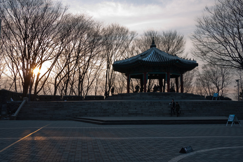 Octagonal pavilion next to N Seoul Tower at early sunset.