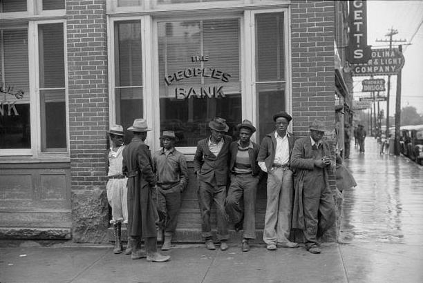 . Men standing on the corner of the main street on rainy Memorial Day. Roxboro, North Carolina, 1940. Jack Delano, Photographer.  Courtesy the Library of Congress