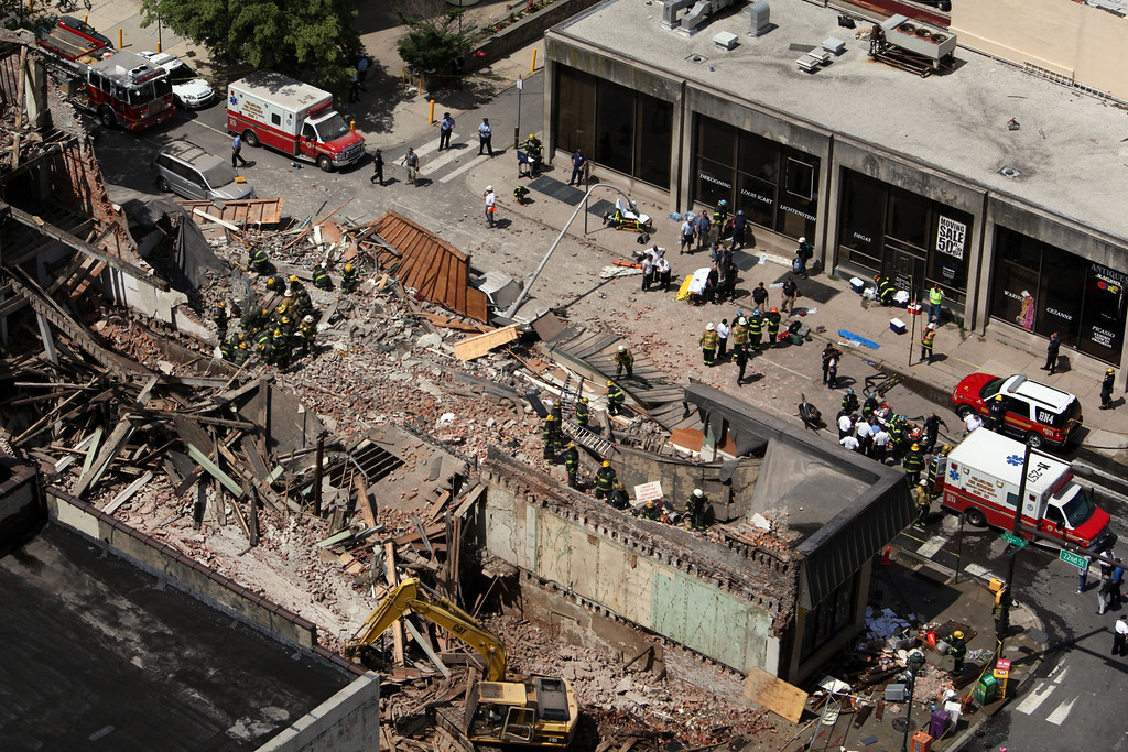 . Rescue personnel work the scene of a building collapse in downtown Philadelphia, Wednesday, June 5, 2013.  A four-story building being demolished collapsed Wednesday on the edge of downtown, injuring 12 people and trapping two others, the fire commissioner said. Rescue crews were trying to extricate the two people who were trapped, and the dozen people who were injured were taken to hospitals with minor injuries, according to city Fire Commissioner Lloyd Ayers. (AP Photo/Jacqueline Larma)
