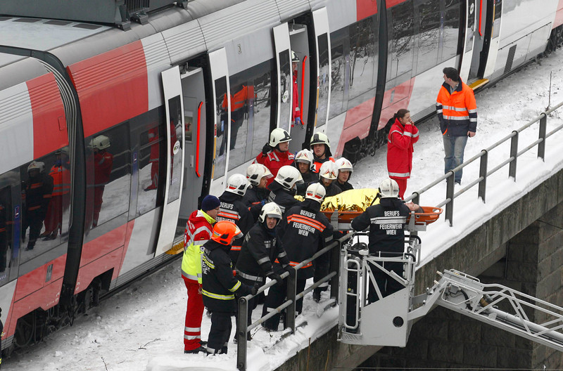 . Austrian rescue personnel carries an injured person in front of two demolished S45 trains after a train crash in Vienna January 21, 2013. Two  trains collided Monday morning, injuring 25 people, police said. REUTERS/Heinz-Peter Bader  (AUSTRIA - Tags: DISASTER TRANSPORT)