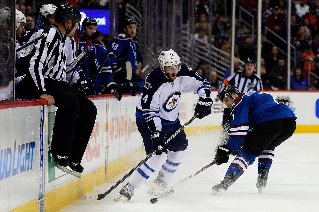 . Anthony Peluso (14) of the Winnipeg Jets skates by John Mitchell (7) of the Colorado Avalanche during the third period of action. The Colorado Avalanche lost 2-1 to the Winnipeg Jets at the Pepsi Center on Sunday, December 29, 2013. (Photo by AAron Ontiveroz/The Denver Post)