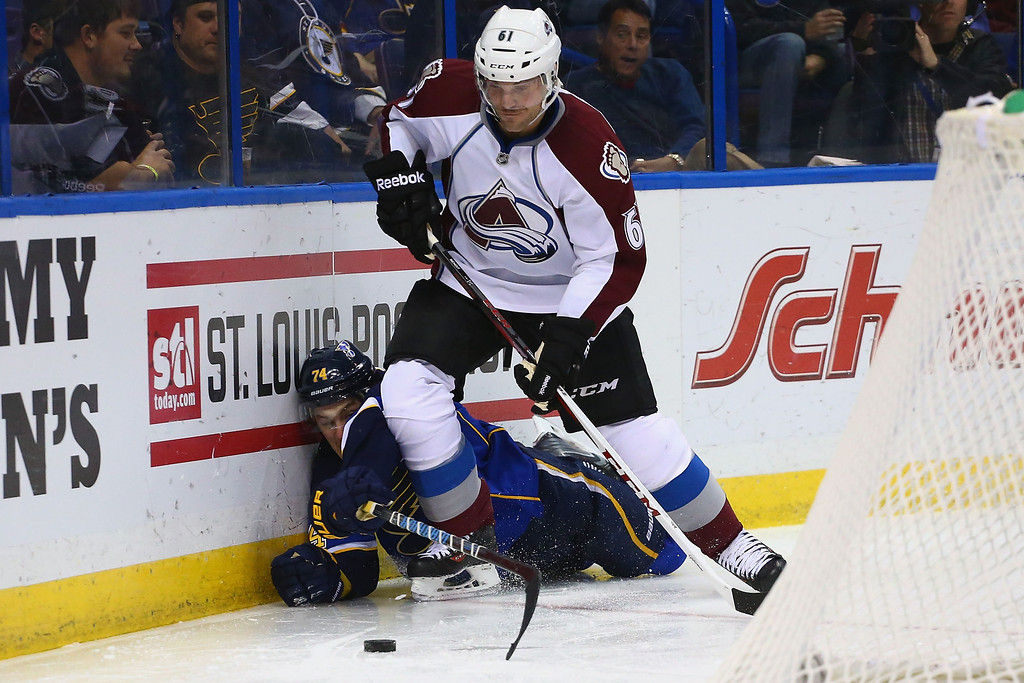 . ST. LOUIS, MO - NOVEMBER 14:  T.J. Oshie #74 of the St. Louis Blues pokes the puck away from Andre Benoit #61 of the Colorado Avalanche at the Scottrade Center on November 14, 2013 in St. Louis, Missouri.  The Blues beat the Avalanche 7-3.  (Photo by Dilip Vishwanat/Getty Images)
