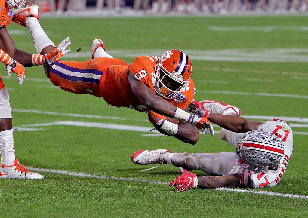 . Clemson running back Wayne Gallman (9) is tackled by Ohio State cornerback C.J. Saunders (17) during the second half of the Fiesta Bowl NCAA college football game, Saturday, Dec. 31, 2016, in Glendale, Ariz. (AP Photo/Rick Scuteri)