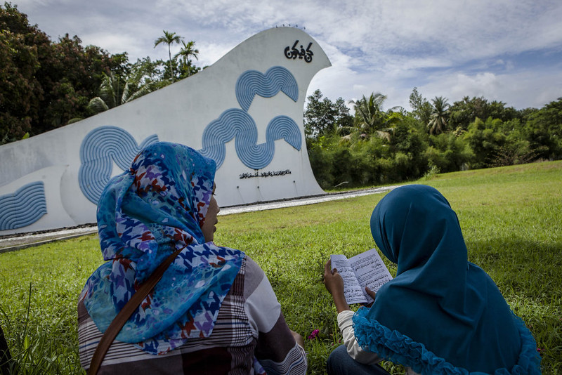 . An Acehnese woman with her daughter reads Quran as they praying at mass grave to commemorate the tenth anniversary of the Boxing Day tsunami on December 26, 2014 in Banda Aceh, Indonesia. Aceh was the worst hit location, being the closest major city to the epicenter of the 9.1 magnitude quake, suffering a huge hit from the following tsunami and resulting in around 130,000 deaths. Throughout the affected region of eleven countries, nearly 230,000 people were killed, making it one of the deadliest natural disasters in recorded history. (Photo by Ulet Ifansasti/Getty Images)