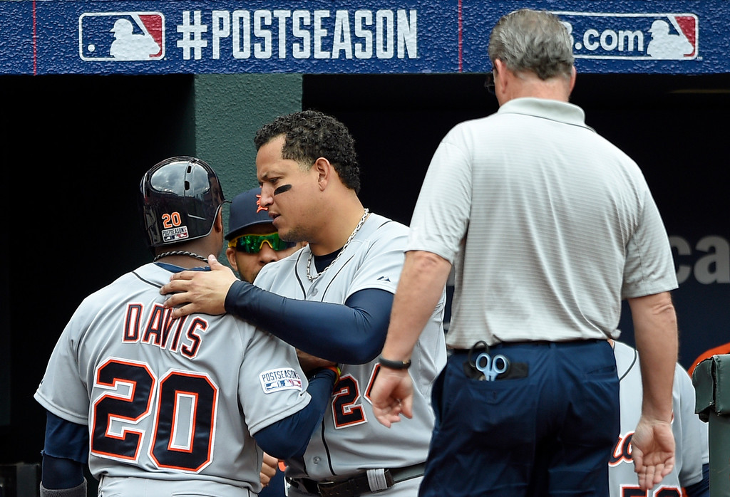 . Detroit Tigers\' Miguel Cabrera, center, speaks with teammate Rajai Davis after Davis was replaced by a pinch runner in the fourth inning of Game 2 in baseball\'s AL Division Series against the Baltimore Orioles in Baltimore, Friday, Oct. 3, 2014. (AP Photo/Nick Wass)
