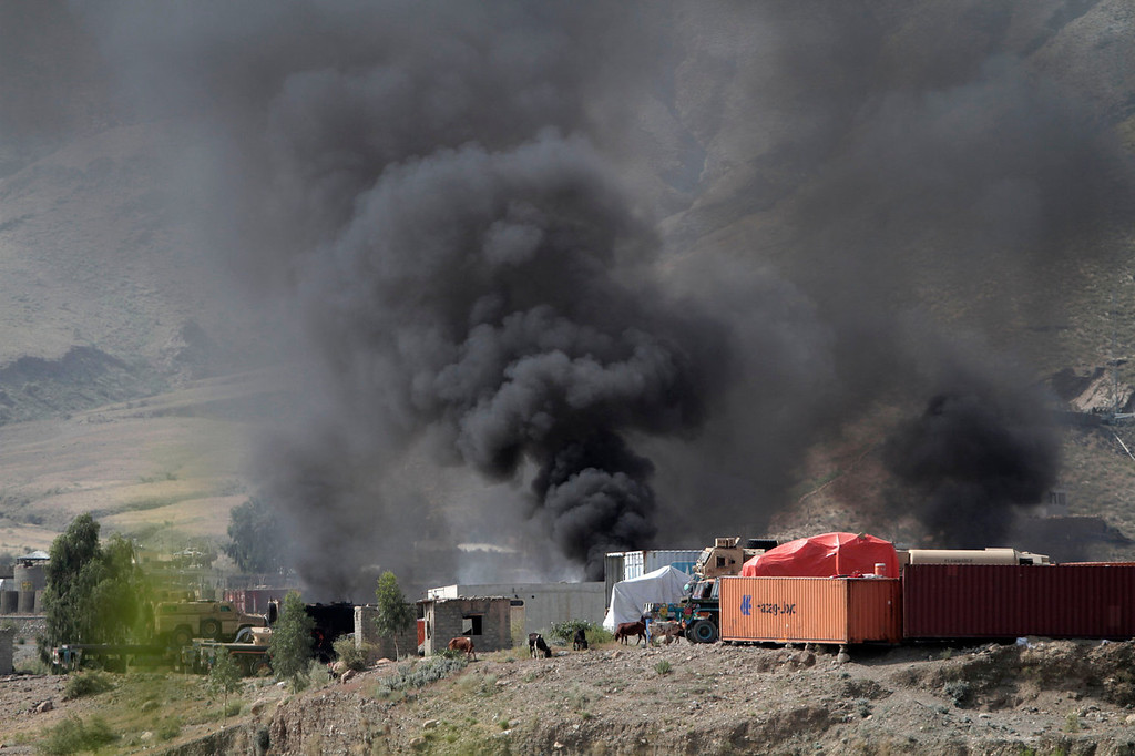 . Smoke rises from a NATO supply truck following an attack by militants in the Torkham area near the Pakistan-Afghanistan border in the Jalalabad province east of Kabul, Afghanistan, Monday, Sept. 2, 2013. The Taliban claimed responsibility for the strike on a U.S. base in Afghanistan near the border with Pakistan on Monday, setting off bombs, torching vehicles and shutting down a key road used by NATO supply trucks, officials said. Several people were killed.   (AP Photo/Rahmat Gul)