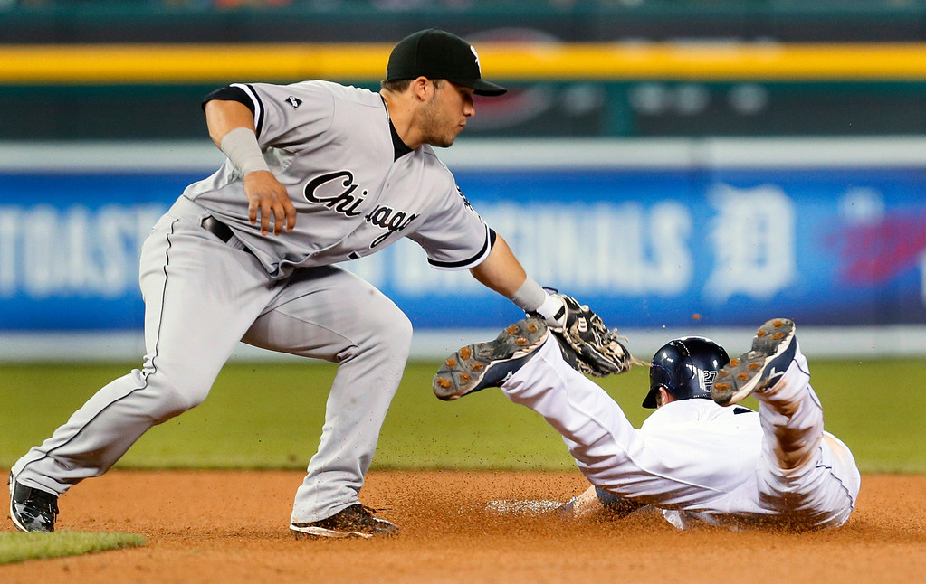 . Detroit Tigers shortstop Andrew Romine steals second base under the tag of Chicago White Sox shortstop Carlos Sanchez in the eighth inning of a baseball game in Detroit Tuesday, Sept. 23, 2014. (AP Photo/Paul Sancya)