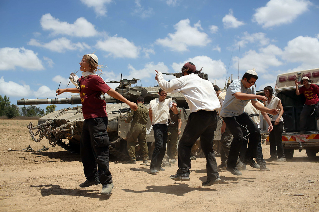 """. Young Orthodox Jews dance to support the soldiers at an army deployment area near Israel\'s border with the Gaza Strip, on July 17, 2014. An Israeli official said the Jewish state had agreed a ceasefire with Hamas that will begin at 0300 GMT Friday, but the Islamist movement said it had \""""no information\"""" on a deal. AFP PHOTO /MENAHEM KAHANA/AFP/Getty Images"""
