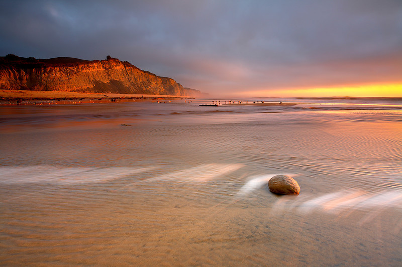 San Gregorio beach is a great place to watch the sunset. This was taken as the first storm of the season caused the water in the river to breach the sand dunes and flow to the sea. Bubbles of sea foam made a line in the sand as the last light came through the fog.