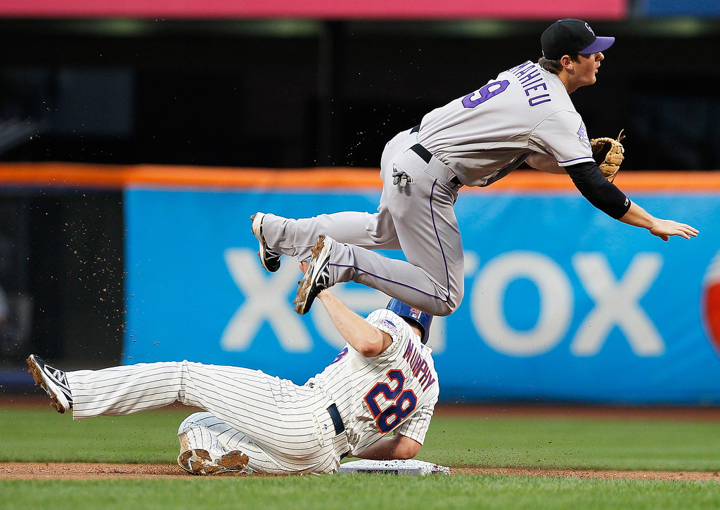 . DJ LeMahieu #9 of the Colorado Rockies leaps over Daniel Murphy #28 of the New York Mets in an attempt to complete a double play in the first inning at Citi Field on August 6, 2013 at Citi Field in the Flushing neighborhood of the Queens borough of New York City.  (Photo by Mike Stobe/Getty Images)