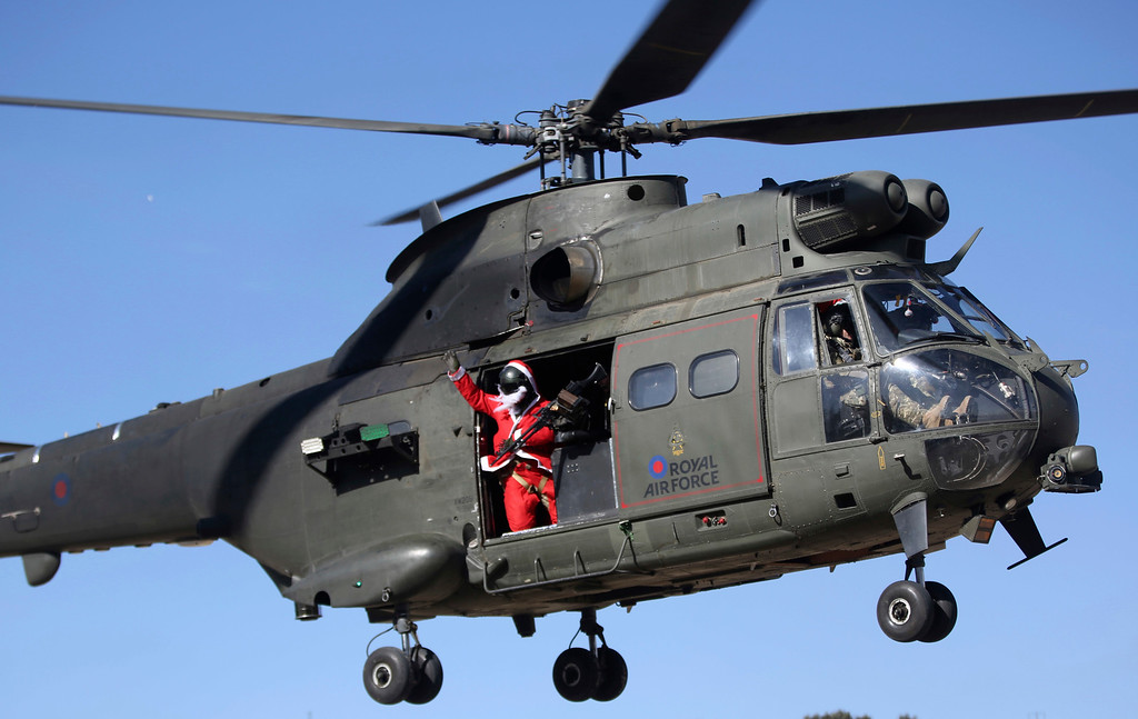 . A British airman dressed as Santa Claus waves from a helicopter to a soccer match between British and German soldiers on Christmas day at Operation Resolute Support headquarters, in Kabul, Afghanistan, Sunday, Dec. 25, 2016. NATO soldiers, Resolute Support mission played a soccer match marking the 102 year anniversary of WW1 in Kabul. The match ended up with British winning the match by (1-0). (AP Photos/Massoud Hossaini)