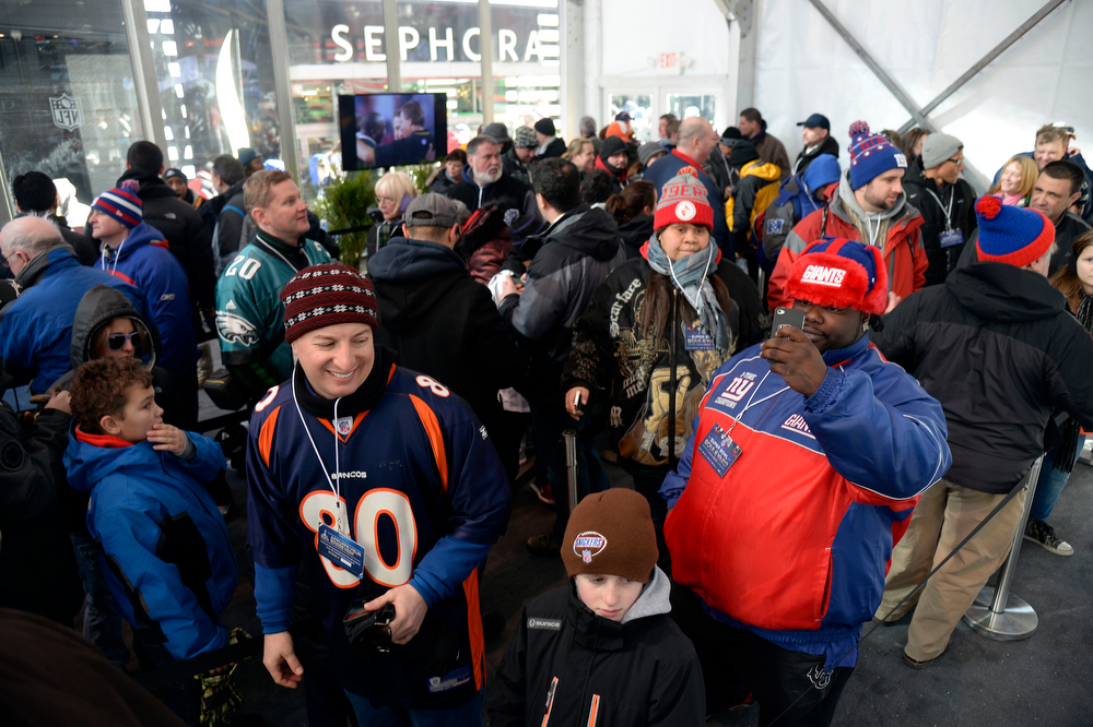 . Super Bowl XLVlll fans hit Times Square and stand n line to get a glimpse of the Vince Lombardi Trophy to enjoy the Super Bowl Boulevard. The NFL transformed a portion of Broadway into the sports and entertainment hub of Super Bowl Week, January 29, 2014. (Photo by John Leyba/The Denver Post)