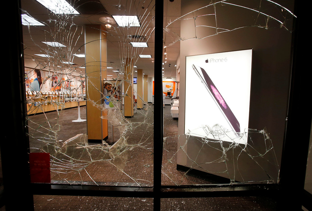 . A trail of broken glass is left by protesters along Shattuck Avenue, including at this AT&T store in Berkeley, Calif., late Sunday evening, Dec. 7, 2014, during a second consecutive night of unrest in the city over the killings of two unarmed black men by police in Ferguson, Mo., and New York. (Karl Mondon/Bay Area News Group)