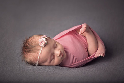 Colour photograph of a newborn baby girl wrapped in a pink wrap with floral headband against a grey backdrop - photographed in home studio