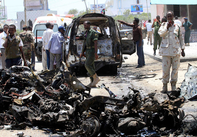 . A Somali soldier uses his mobile phone to record the wreckage of vehicles at the scene of an explosion near the presidential palace in Somalia\'s capital Mogadishu March 18, 2013. A car bomb exploded near the presidential palace in the Somali capital Mogadishu on Monday, killing at least 10 people in a blast that appeared to target senior government officials, police said. REUTERS/Omar Faruk