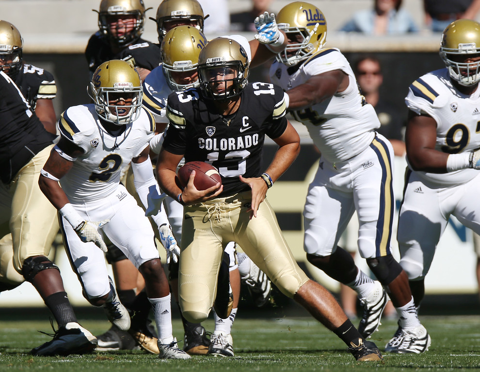 . Colorado quarterback Sefo Liufau, right, runs for yardage as UCLA  defensive back Jaleel Wadood (2) chases in the first quarter of an NCAA college football game in Boulder, Colo., Saturday, Oct. 25, 2014. (AP Photo/David Zalubowski)