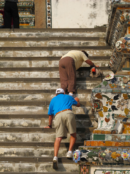 Wat Aroon (Temple of Dawn)  Renee Mirsky being encouraged by Burt Rein as she does the moon walk descending the steep shallow steps of the pagoda.  Thanks Burt.