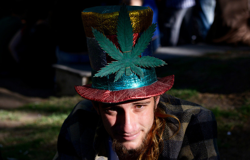 . A demonstrator wears a top hat emblazoned with an image of a marijuana leaf as activists gathered in support of the legalization of marijuana outside the Congress building in Montevideo, Uruguay, Tuesday, Dec. 10, 2013. Uruguay\'s Senate gave final congressional approval Tuesday to create the world\'s first national marketplace for legal marijuana, an audacious experiment that will have the government oversee production, sales and consumption of a drug illegal almost everywhere else. (AP Photo/Matilde Campodonico)