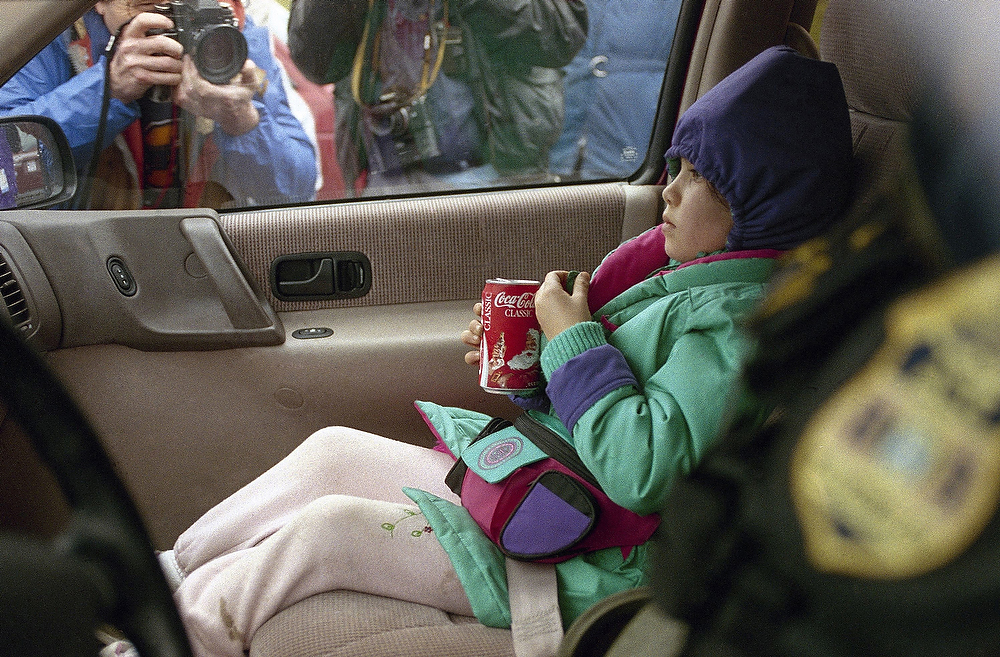 . A young child rides in the back of a Bureau of Alcohol Tobacco and Firearms van out of the Mount Carmel compound of Branch Davidians cult in Waco, Texas on Monday, March 1, 1993. So far, 10 children have been let go after police negotiations with the cult began. Authorities said at least 75 persons remain in the compound. (AP Photo/Derek Lloyd Lovelock, right, and Renos Avraam)