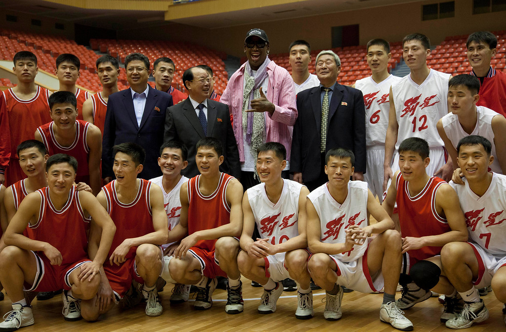 . Former NBA basketball star Dennis Rodman poses for pictures with North Korean basketball players during a practice session in Pyongyang, North Korea on Friday, Dec. 20, 2013. Rodman selected the members of the North Korean team who will play in Pyongyang against visiting NBA stars on Jan. 8, 2014, the birthday of North Korean leader Kim Jong Un. (AP Photo/David Guttenfelder)