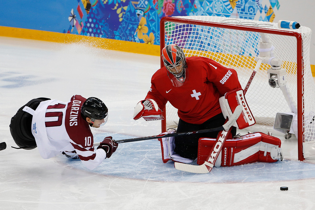 . Switzerland goaltender Jonas Hiller blocks Latvia forward Lauris Darzins\'s shot at the gold during the first period of the 2014 Winter Olympics men\'s ice hockey game at Shayba Arena, Wednesday, Feb. 12, 2014, in Sochi, Russia. (AP Photo/Petr David Josek)