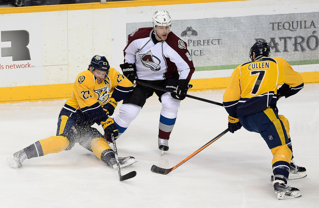 . Nashville Predators forward Patric Hornqvist (27), of Sweden, passes the puck to teammate Matt Cullen (7) as he is defended by Colorado Avalanche defenseman Jan Hejda (8), of Czech Republic, in the first period of an NHL hockey game on Tuesday, March 25, 2014, in Nashville, Tenn. (AP Photo/Mark Zaleski)