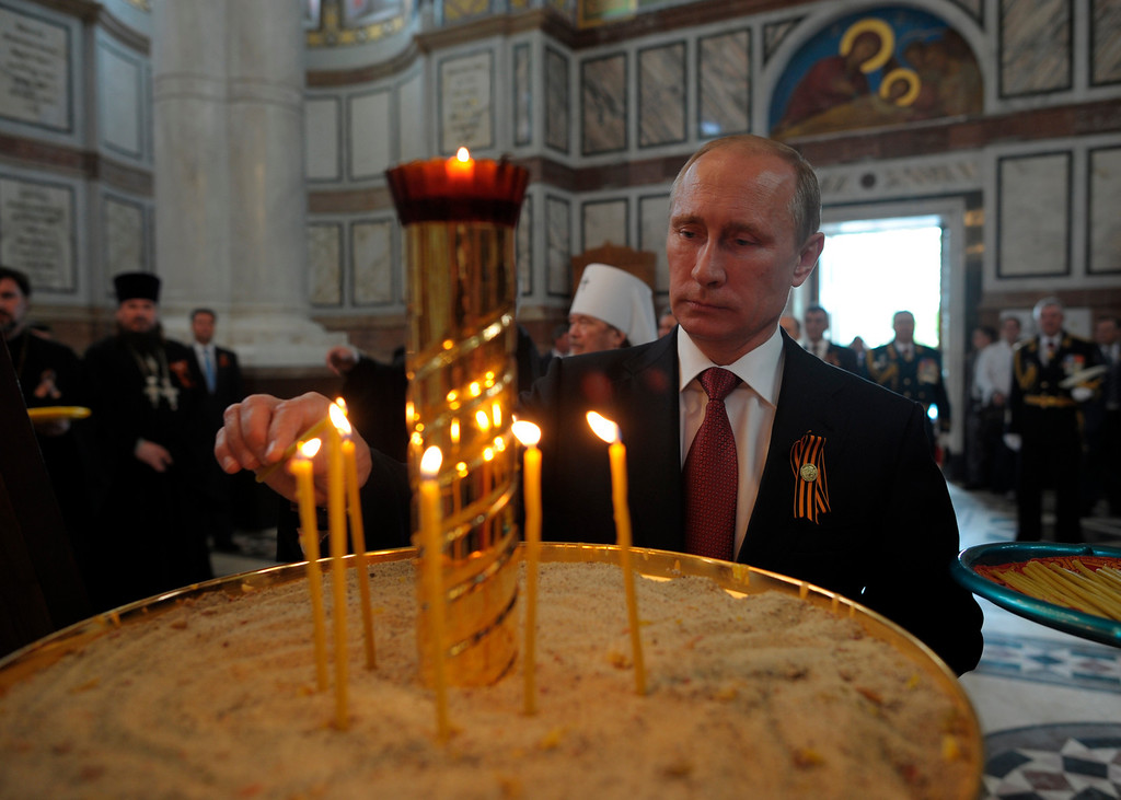 . Russian President Vladimir Putin lights a candle in St. Vladimir\'s Cathedral in Sevastopol where he attends celebrations marking  the Victory Day, Crimea, Friday, May 9, 2014. (AP Photo/RIA-Novosti, Alexei Druzhinin, Presidential Press Service)