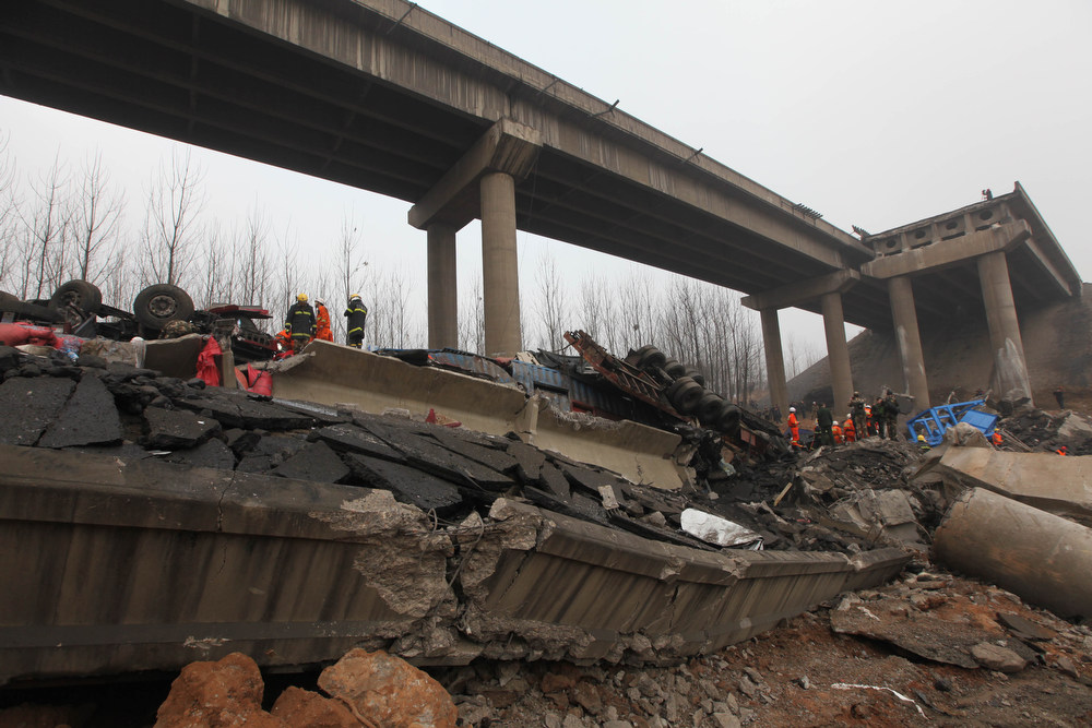 Description of . Rescuers work at the scene of the collapsed Yichang bridge near the city of Sanmenxia, central China's Henan province, on February 1, 2013 after a fireworks-laden truck exploded as it crossed the bridge killing 26 people as the structure collapsed and vehicles plummeted to the ground, state-run media reported. An 80-meter long part of the bridge collapsed and six vehicles had been retrieved from the debris, China's official news agency Xinhua said. The bridge near the city of Sanmenxia is on the G30 expressway, the longest road in China, which stretches for nearly 4,400 kilometers (2,700 miles) from China's western border with Kazakhstan to the eastern Yellow Sea. AFP PHOTO STR/AFP/Getty Images