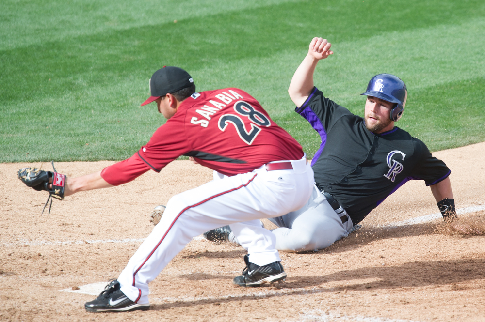 . Alex Sanabia #28 of the Arizona Diamondbacks tags out Jackson Williams #72 of the Colorado Rockies at home plate during a spring training game at Salt River Fields at Talking Stick on February 28, 2014 in Scottsdale, Arizona. (Photo by Rob Tringali/Getty Images)