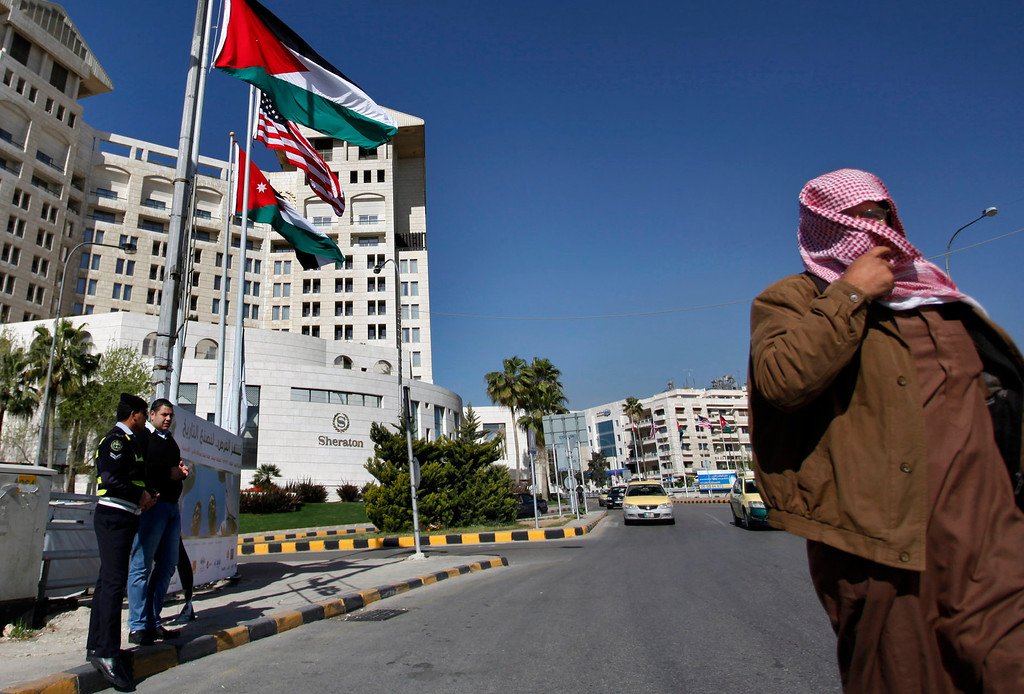 . Jordanian traffic policemen stand under poles, with flags representing The United States of America and Jordan, a day before US President Barack Obama\'s visit to the kingdom, in Amman, Jordan, Thursday, March 21, 2013. (AP Photo/Mohammad Hannon)