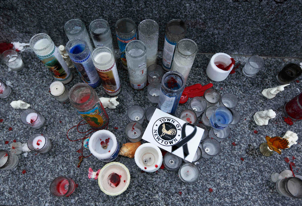 ". Candles and a sticker are seen honoring the victims of the Sandy Hook Elementary school shootings in Newtown, Connecticut December 17, 2012. The small Connecticut town shattered by an act President Barack Obama called ""unconscionable evil,\"" holds on Monday the first two of 20 funerals for schoolchildren massacred in their classrooms last week.   REUTERS/Shannon Stapleton"