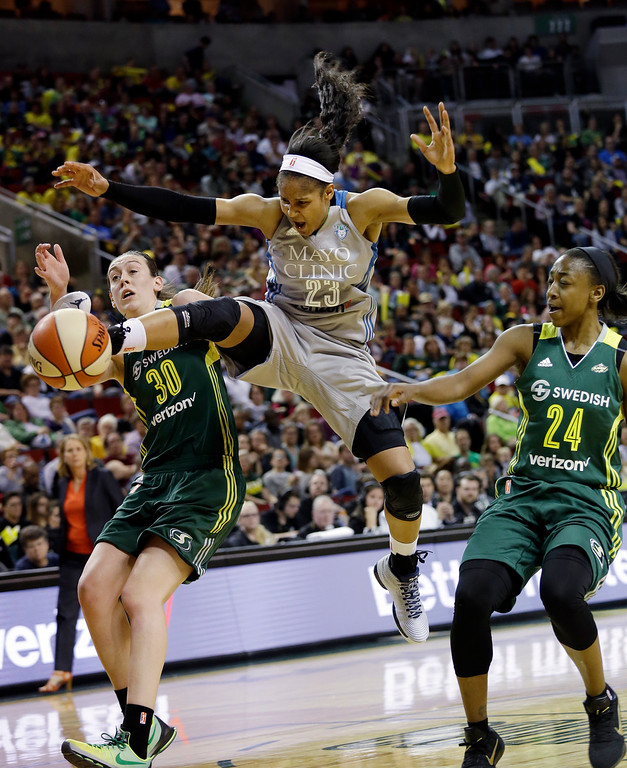 . Minnesota Lynx\'s Maya Moore (23) loses the ball on a drive between Seattle Storm\'s Breanna Stewart (30) and Jewell Loyd (24) in the first half of a WNBA basketball game Sunday, May 22, 2016, in Seattle. (AP Photo/Elaine Thompson)