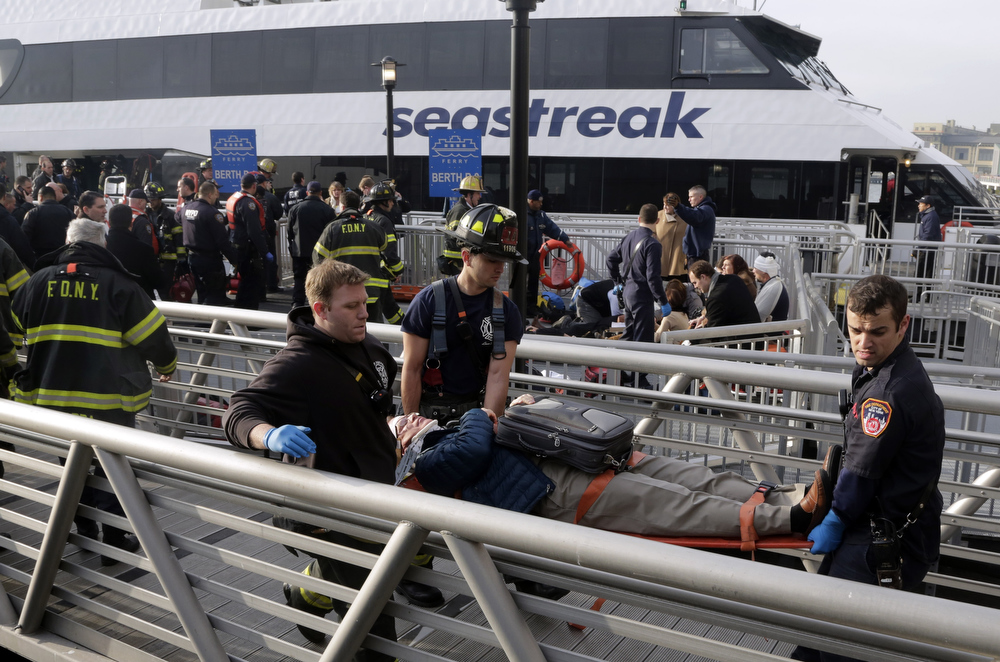 Description of . New York City firefighters remove an injured passenger of the Seastreak Wall Street ferry, in New York,  Wednesday, Jan. 9, 2013. The Seastreak Wall Street ferry from Atlantic Highlands, N.J., banged into the mooring as it arrived at South Street in lower Manhattan during morning rush hour, injuring as many as 50 people, at least one critically, officials said. (AP Photo/Richard Drew)