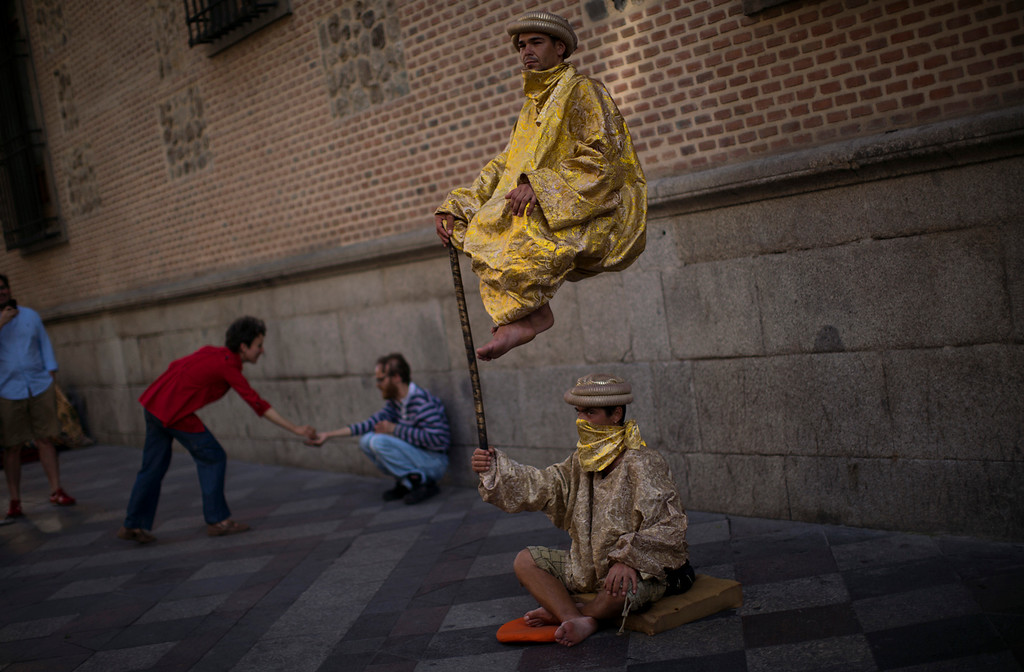 . Men performance as they beg for charity in a street in Madrid, Spain,  Monday, May 14, 2012. Spain got caught up in the uncertainty surrounding the European single currency and the electoral stalemate in Greece Monday as it saw its borrowing costs rise and stock prices fall at alarming rates. (AP Photo/Emilio Morenatti)
