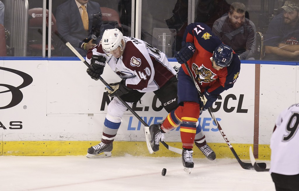. Colorado Avalanche\'s Alex Tanguay (40) and Florida Panthers\' Derek MacKenzie (40) fight for the puck during the third period of an NHL hockey game, Thursday, Jan. 15, 2015 in Sunrise, Fla. The Avalanche won 4-2. (AP Photo/J Pat Carter)
