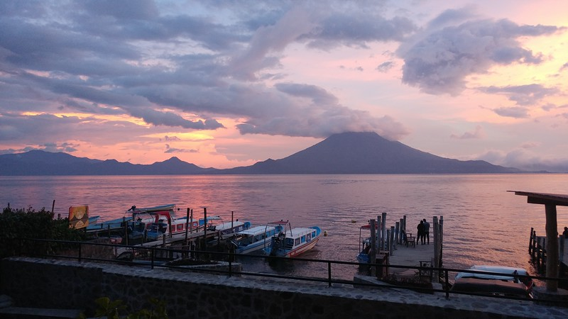 a sunset on the water with boats tied up to a dock and a volcano in the background