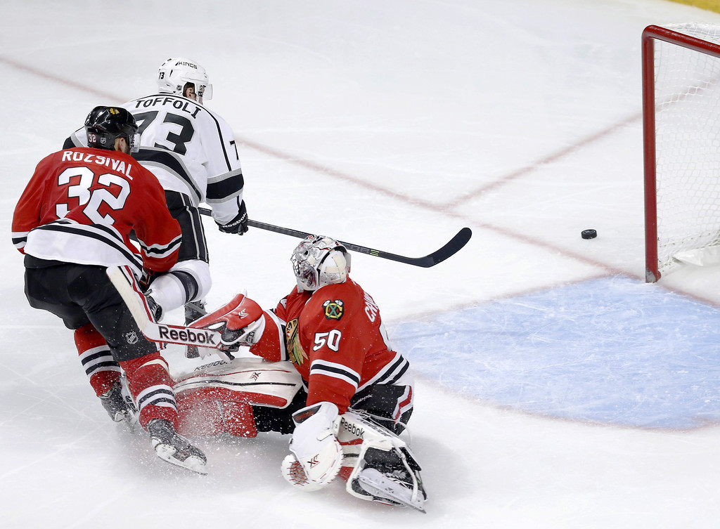. Los Angeles Kings center Tyler Toffoli (73) watches his shot on goal hit the post past Chicago Blackhawks goalie Corey Crawford (50) as Michal Rozsival watches during the third period of Game 1 of the Western Conference finals in the NHL hockey Stanley Cup playoffs in Chicago on Sunday, May 18, 2014. (AP Photo/Charles Rex Arbogast)