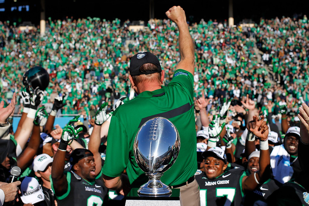 . DALLAS, TX - JANUARY 01:  Head Coach Dan McCarney of the North Texas Mean Green celebrates with his team after defeating the UNLV Rebels in the Heart of Dallas Bowl at Cotton Bowl Stadium on January 1, 2014 in Dallas, Texas. The North Texas Mean Green defeated the UNLV Rebels 36-14.  (Photo by Sarah Glenn/Getty Images)