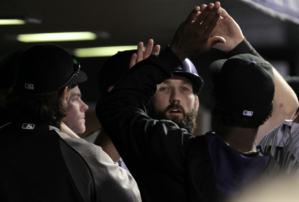 . Colorado Rockies\' Jason Pridie is congratulated in the dugout after he scored in the 11th inning of a baseball game against the Chicago Cubs in Denver on Tuesday, Aug. 5, 2014. (AP Photo/Joe Mahoney)