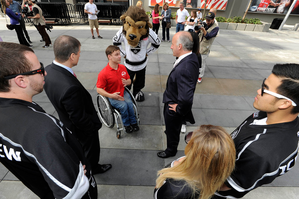 """. Ryan Chalmers talks with members of the LA Kings. Chalmers is pushing himself in a wheel chair on a coast-to-coast trip that starts at the JW Marriott in Los Angeles, and will end in New York\'s Central Park. The 3000 mile odysey will raise funds for an organization called  \""""Stay Focused\"""" that allows teens and young adults with disabilities to participate in sports alongsid able-bodied people.  Los Angeles CA 4/6/2013(John McCoy/Staff Photographer"""