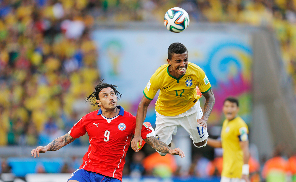 . Brazil\'s Luiz Gustavo and Chile\'s Mauricio Pinilla go for a header during the World Cup round of 16 soccer match between Brazil and Chile at the Mineirao Stadium in Belo Horizonte, Brazil, Saturday, June 28, 2014. (AP Photo/Frank Augstein)