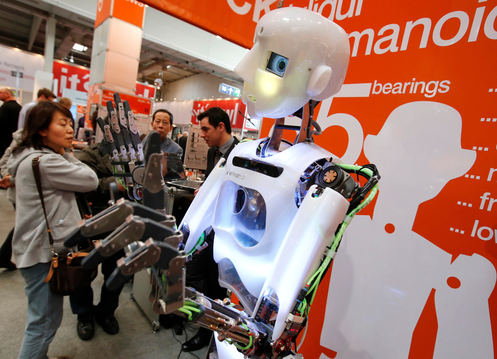 Description of . A humanoid robot made by Igus gestures at the Hanover Messe on the first day of the industrial trade fair, in Hanover April 8, 2013. The Hanover fair runs from April 8 -12. REUTERS/Fabrizio Bensch