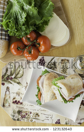 stock-photo-turkey-sub-on-rustic-bread-with-tomato-bread-lettuce-and-cheese-overhead-view-123132640.jpg