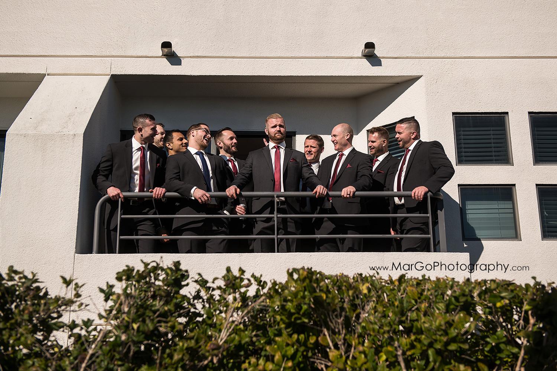 groom and groomsmen in suits at balcony in San Diego Hyatt Regency Mission Bay Hotel