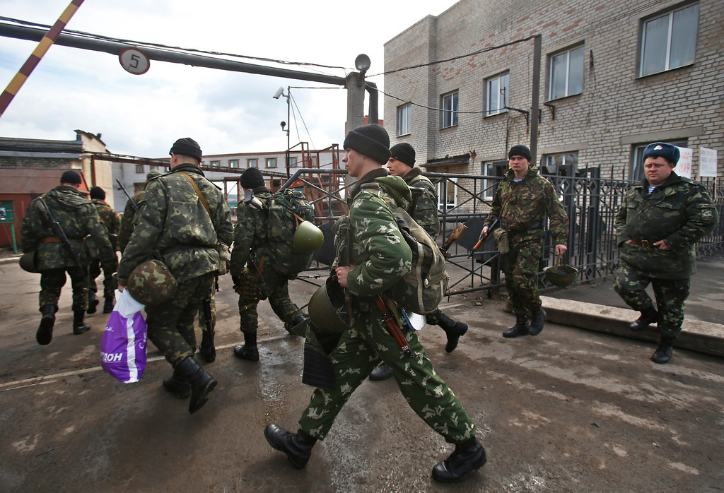 . Soldiers walk near the armory of the Ukrainian army in the village of Poraskoveyevka, eastern Ukraine, Thursday, March 20, 2014.  (AP Photo/Sergei Grits)
