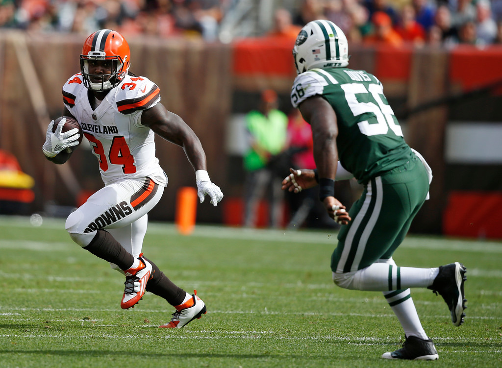 . Cleveland Browns running back Isaiah Crowell (34) avoids New York Jets inside linebacker Demario Davis (56) during the first half of an NFL football game, Sunday, Oct. 8, 2017, in Cleveland. (AP Photo/Ron Schwane)