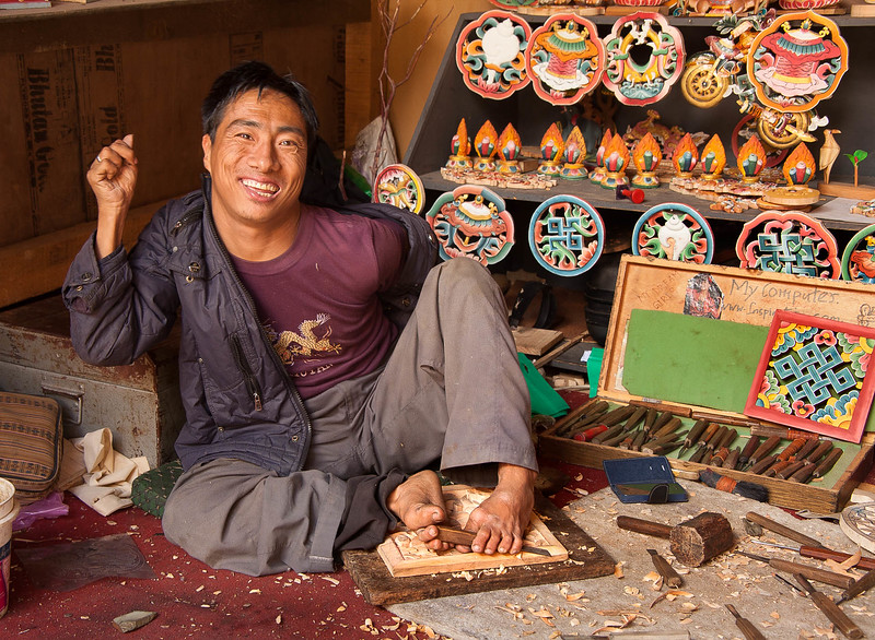 Mr. Pema Tshering who carves and paints with his feet as his hands are rendered uncontrollable by cerebral palsy, Thimphu, Bhutan.