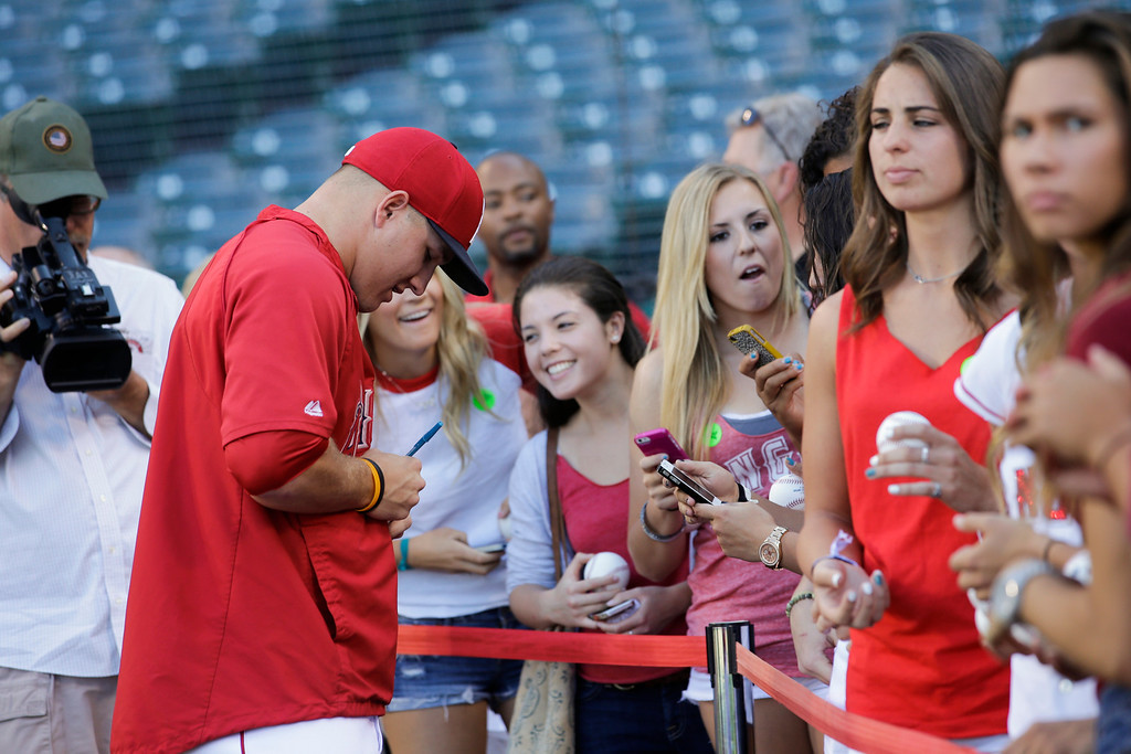 . Los Angeles Angels\' Mike Trout, left, sighs his autographs before a baseball game against the Houston Astros on Friday, Aug. 16, 2013, in Anaheim, Calif. (AP Photo/Jae C. Hong)