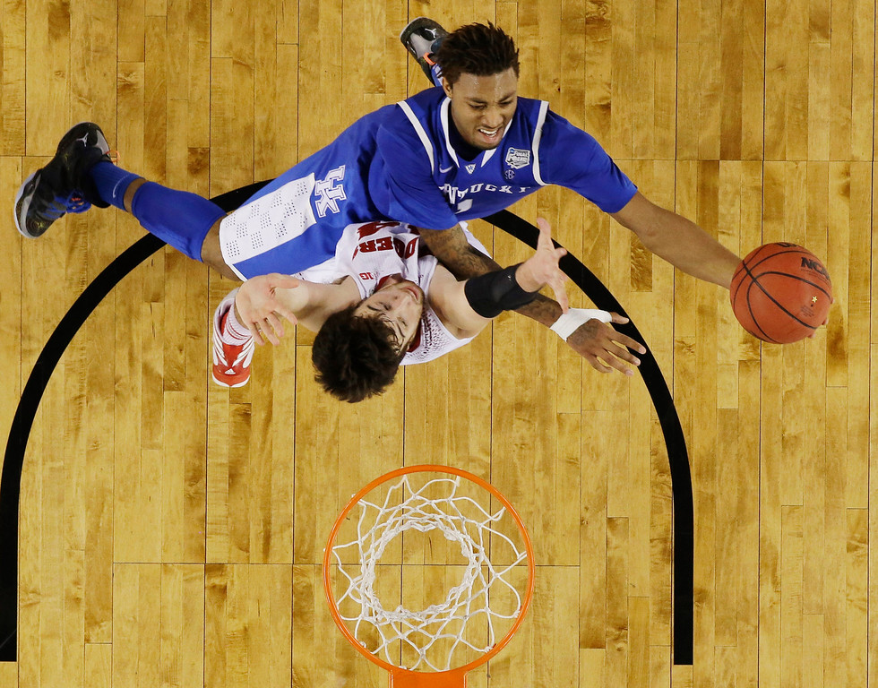 . Kentucky guard James Young shoots against Wisconsin forward Frank Kaminsky during the second half of the NCAA Final Four tournament college basketball semifinal game Saturday, April 5, 2014, in Arlington, Texas. (AP Photo/David J. Phillip)