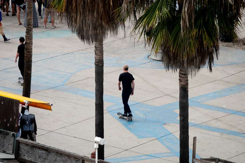 A skateboarder rolls along Windwar Avenue in Venice Beach